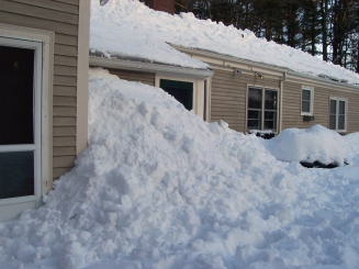 Buildup of snow in the back yard from using the roof rake