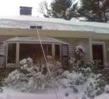 Removing snow from a roof with a roof rake
