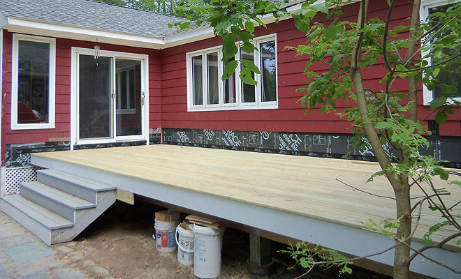 Pressure-treated decking has been installed. We are able to re-use the stairs, which were rebuilt a year ago. The code requires stair rails when there are four rises, and deck railing when the deck exceeds 30