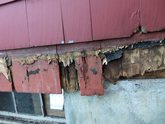 The deck was installed over the siding, without flashing. No bolts were used, and the nails had almost all rusted away. The shingles and sheathing were quite rotted, and we also had to replace some small sections of the framing.